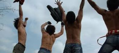 a scene from rang de basant where three biys are looking at the sky waiving their hands in the air