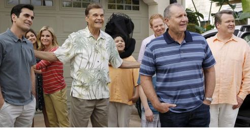 in photo a still from the show modern family, the whole caste standing outside the home