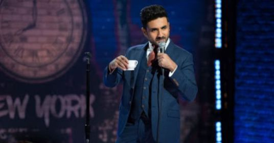 vir das performing a set of stand up comedy holding a cup of tea
