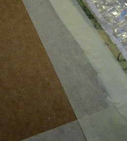 Cardboard 'stretcher' for glued, taped and padded fabric