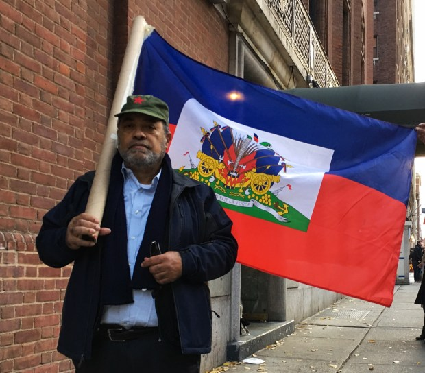 Labor organizer Ray Laforest, 69, carries Haitian flag near Castro memorial at the Mission of Cuba to the United Nations in midtown Manhattan.