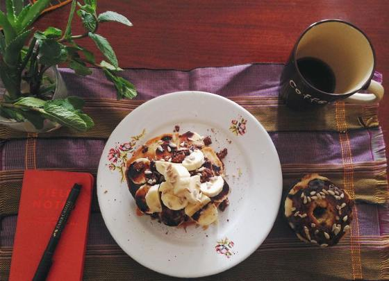 Pancakes, donut, coffee mug, notebook and basil plant