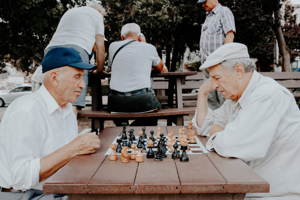 elderly people playing chess by Vlad Sargu
