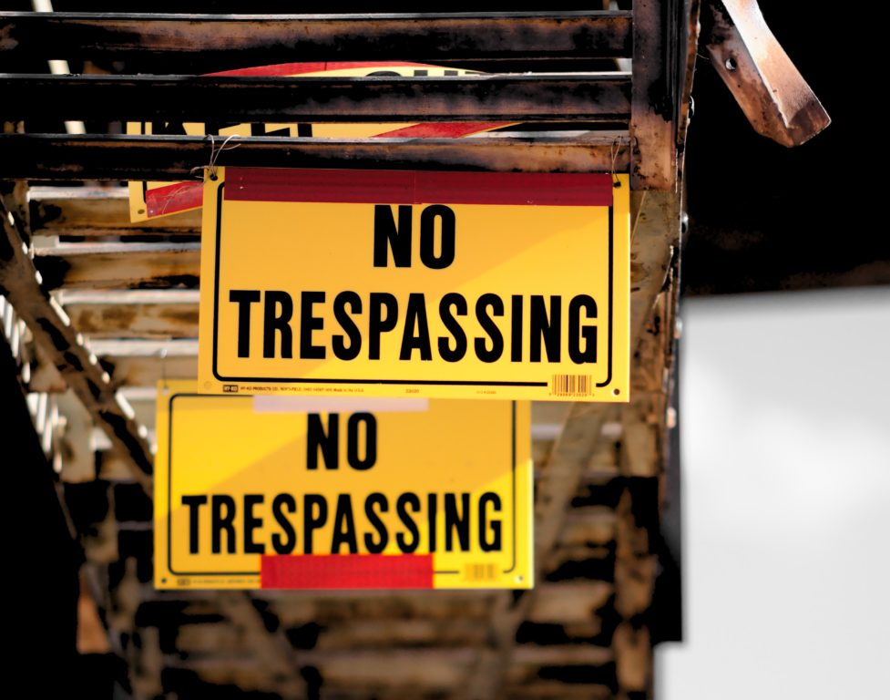 NO TRESPASSING signs hanging from a fire escape on a downtown building by michael-dziedzic