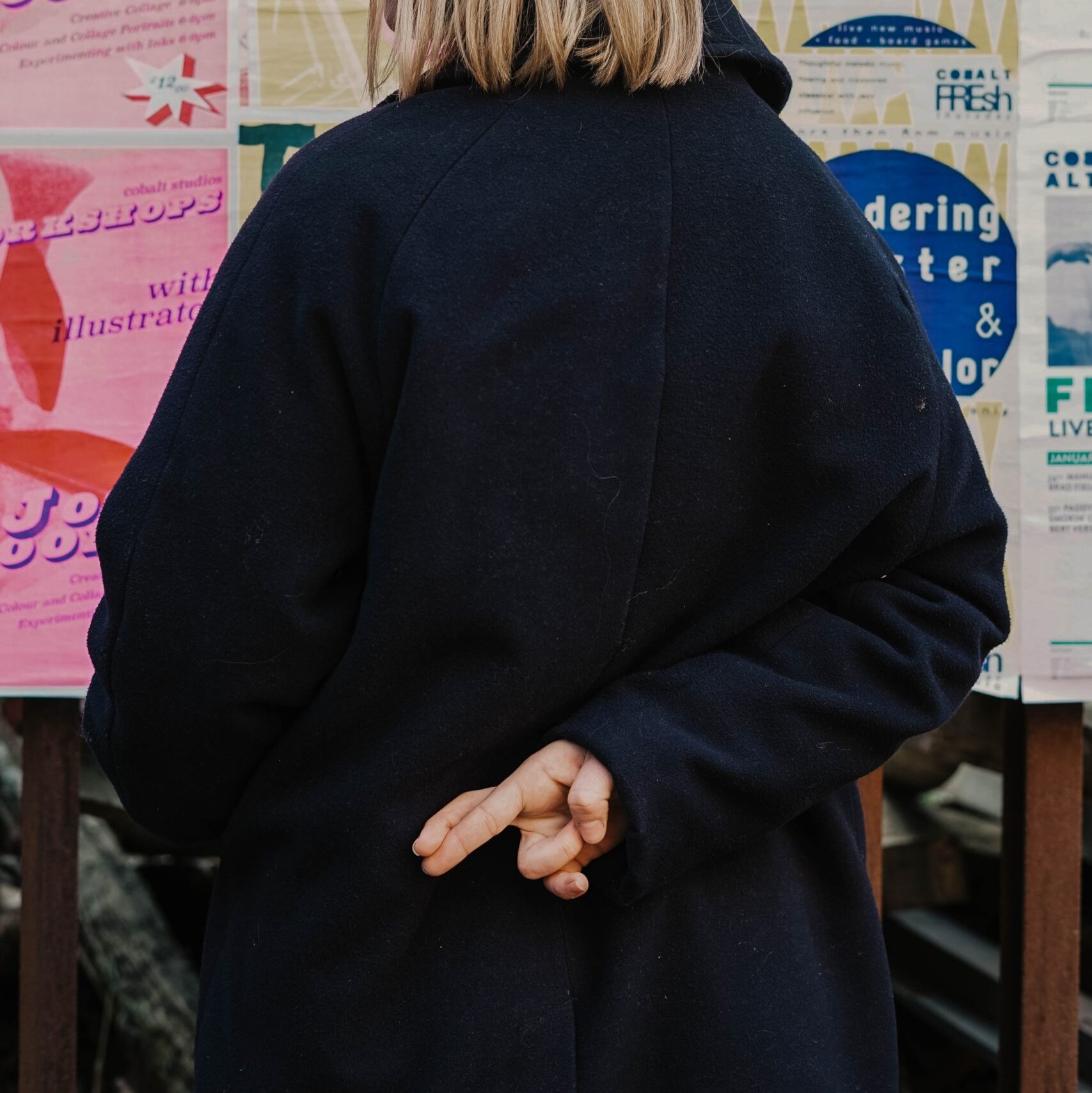 woman in blue hoodie standing in front of white and red kanji text signage brutal honesty Photo by Toa Heftiba on Unsplash
