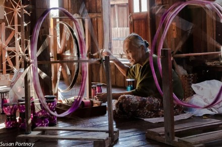 A old woman spins lotus flower silk in a small factory on Inle Lake