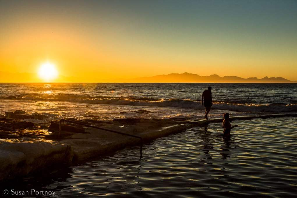 Stunning Silhouette Photos Guaranteed to Inspire Your Travels-Sunrise over the ocean and near a swimming area where two people in silhouetter are wading through the water. Cape Town, South Africa.