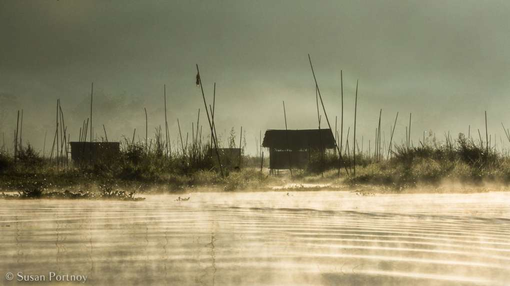 Stunning Silhouette Photos Guaranteed to Inspire Your Travels-Beautiful, misty view of floating garden with a gardener's hut, on Inle Lake in Myanmar.