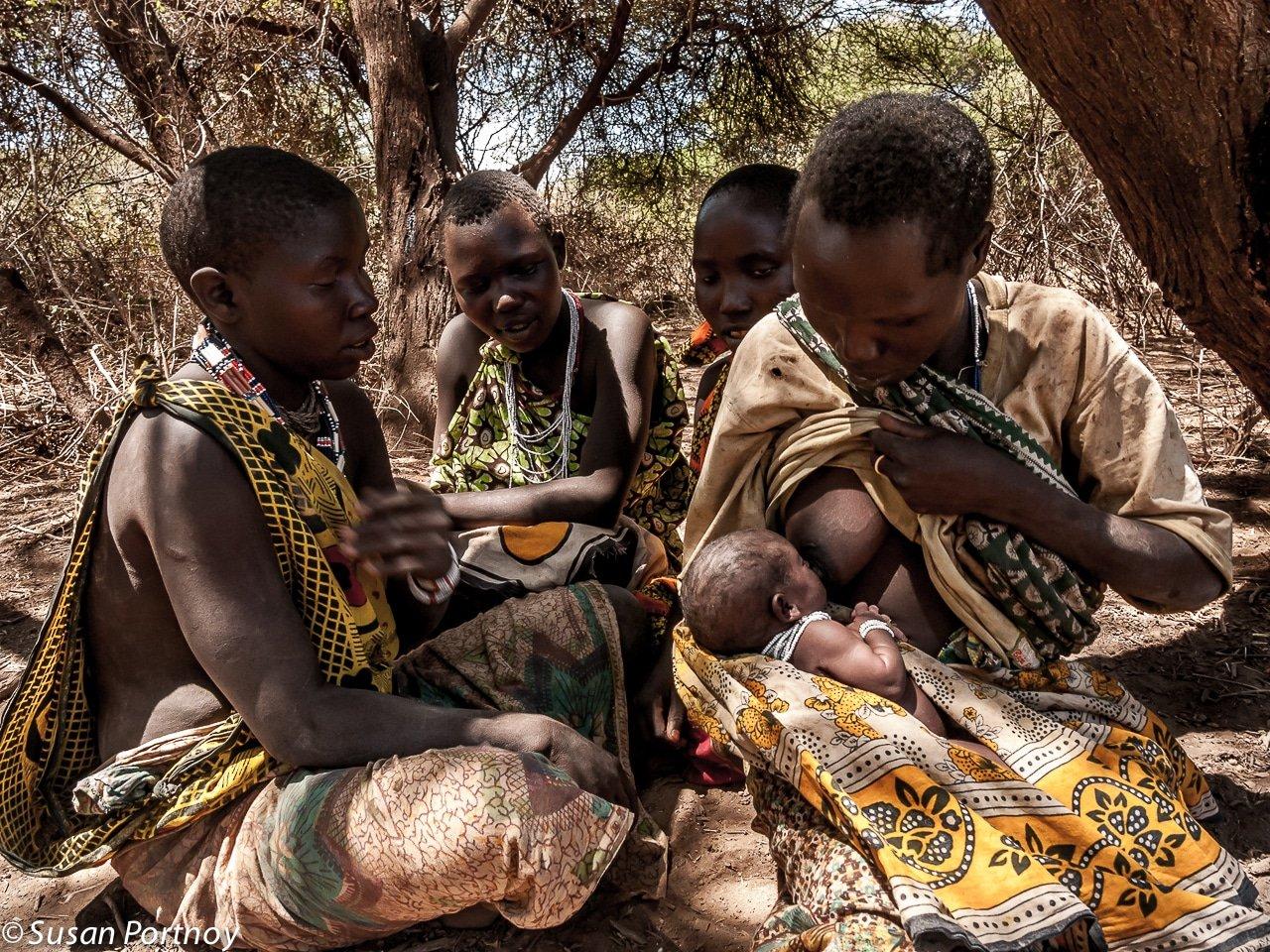 Hadzabe woman nurses infant in Tanzania