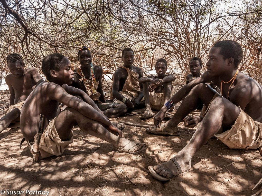 Hadzabe men sit in a clearing in Tanzania