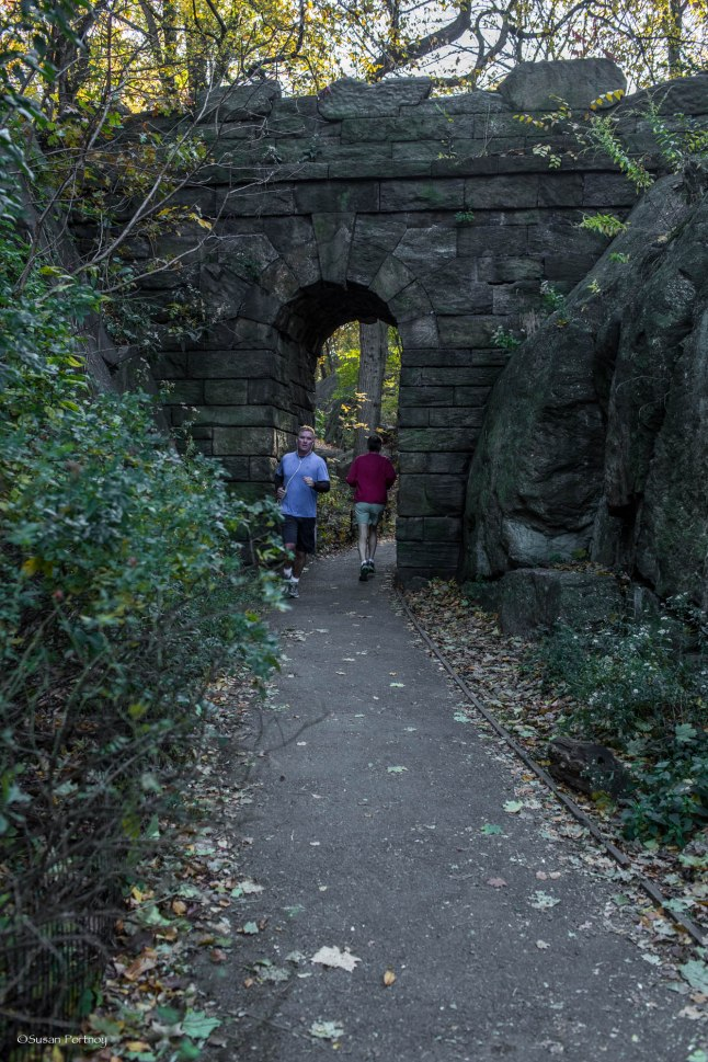 Early morning joggers pass through the Ramble Stone Arch