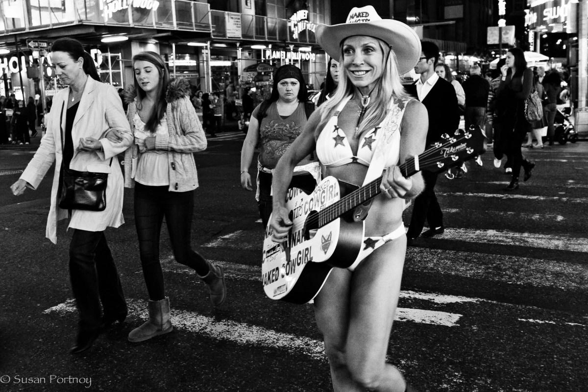 Woman playing guitar playing bikini in Times Square