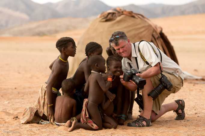 A fellow traveler shows the Himba children their photos on his LCD