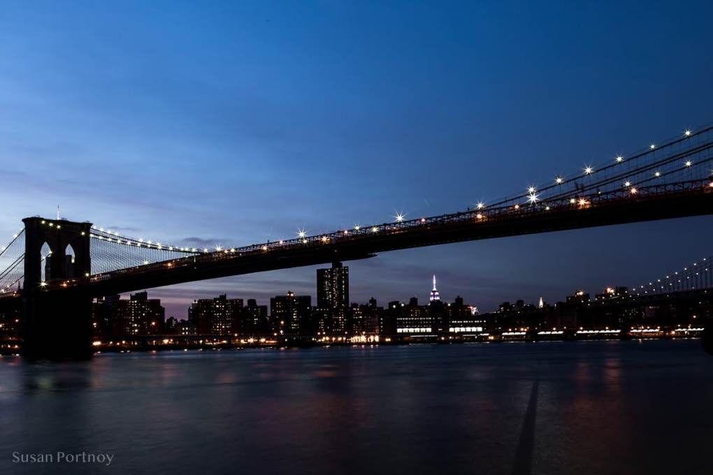 View of the Brooklyn Bridge with the Empire State Building in the background at night during blue hour. f