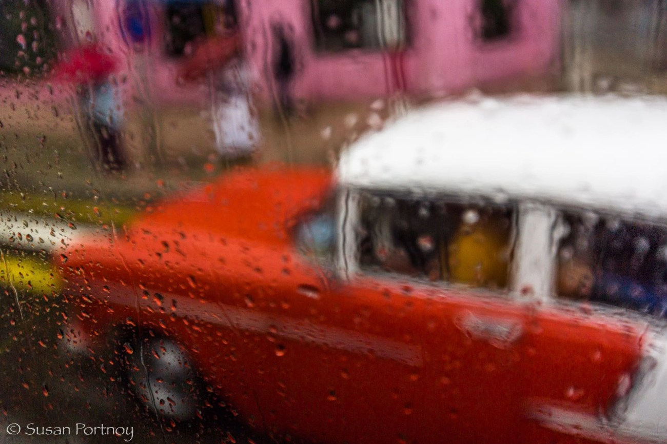 Red classic car in Havana, Cuba as seen through a rainy window