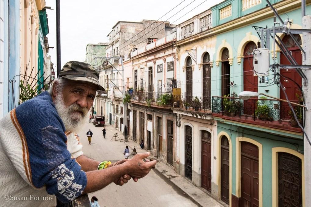 Cuban man on a balcony in Central Havana, Cuba