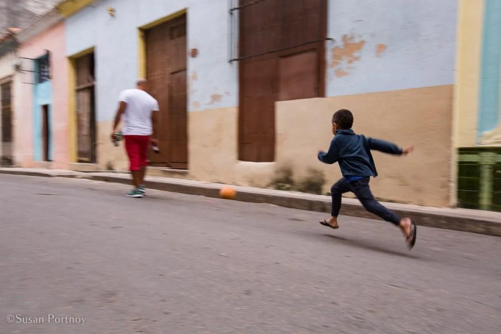 Child kicking a ball in Old Havana, Cuba