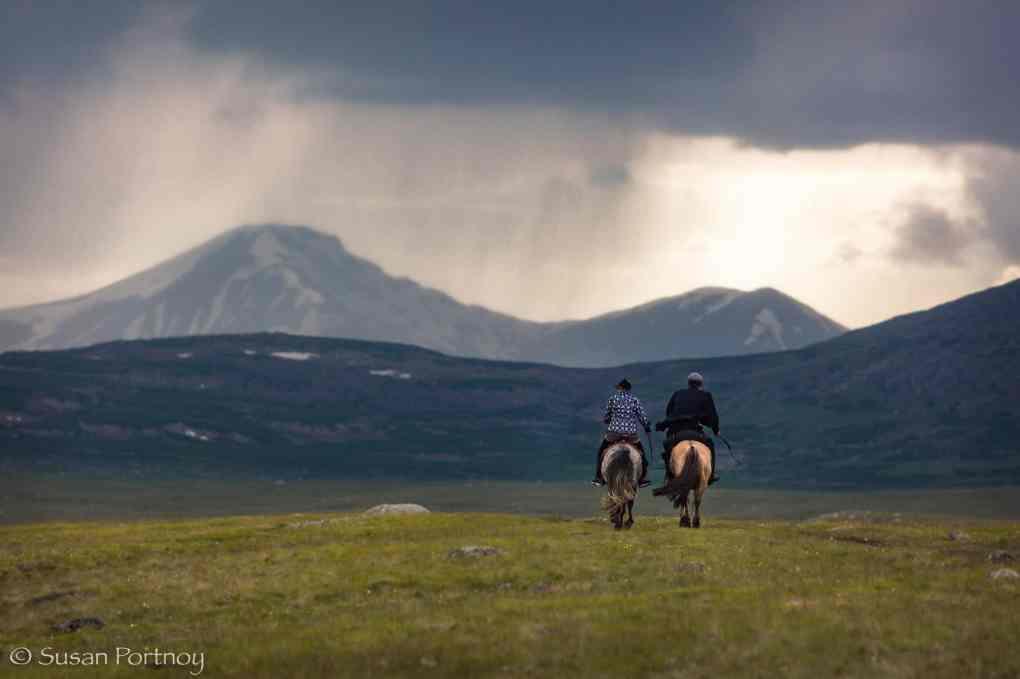 Two Kazaks riding horses in the mountains of theAltai Tavan Bogd National Park, Mongolia