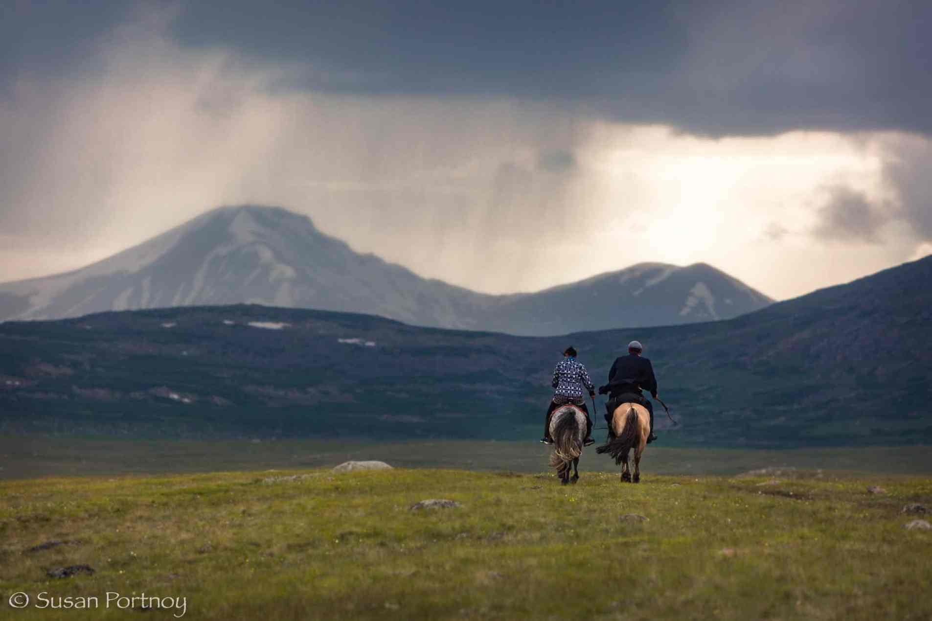 Two Kazaks riding horses in the mountains of theAltai Tavan Bogd National Park, Mongolia