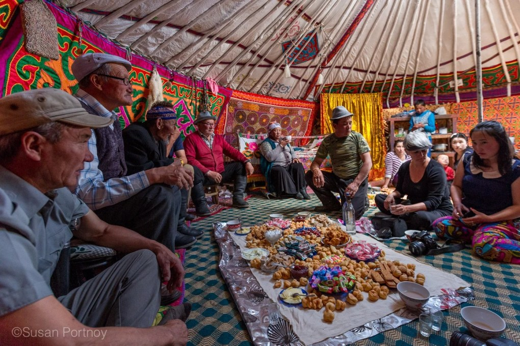 Mongolians lay out food for a Kazakh Mongolian Dance Party - The Insatiable Traveler