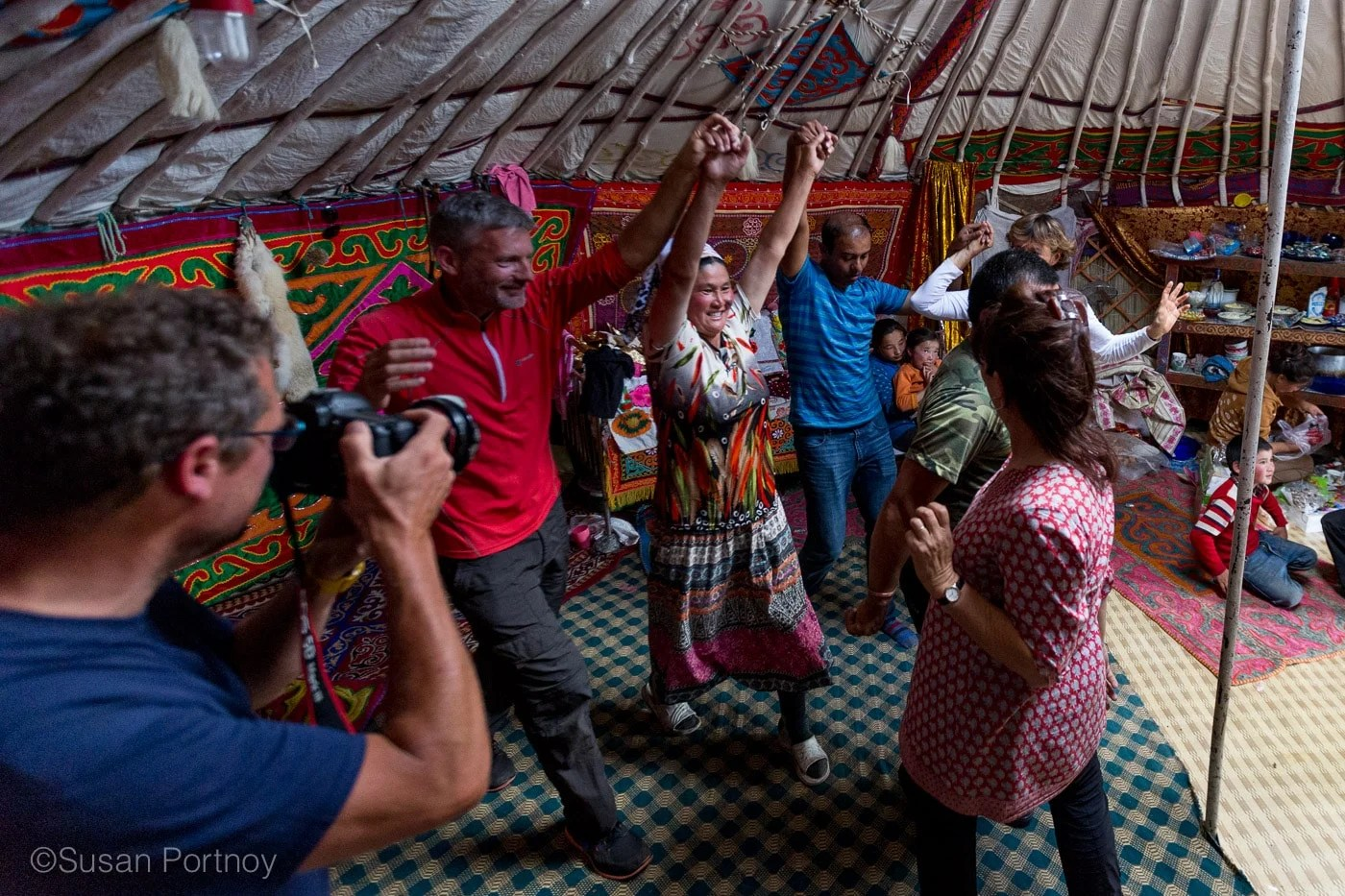 People dancing in a line holding hands at a Kazakh Mongolian Dance Party - The Insatiable Traveler