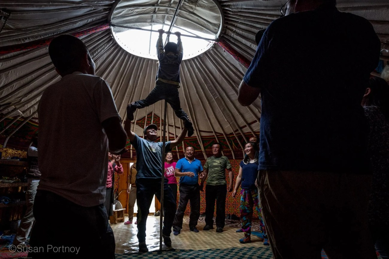 A boy climbs the pole of a ger at a Kazakh Mongolian Dance Party - The Insatiable Traveler