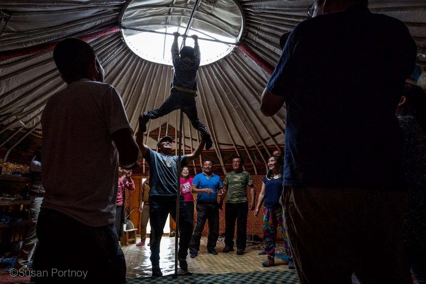 A boy climbs the pole of a ger at a Kazakh Mongolian Dance Party - The Insatiable Traveler