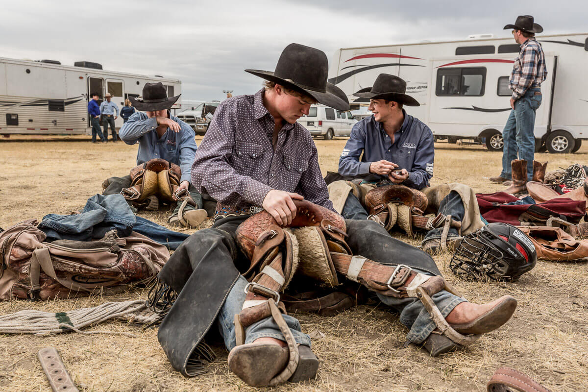 Cowboys getting their saddles ready for a rodeo