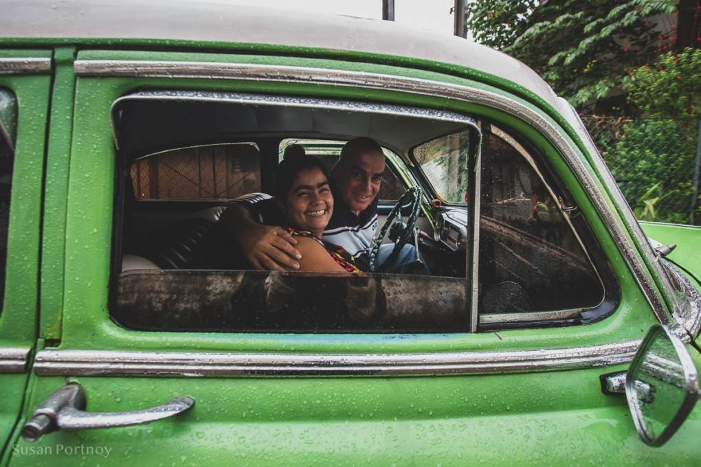 Couple in a vintage green car in Bejucal, Cuba