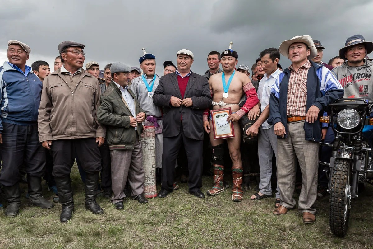 The winning wrestlers. You can see the horse and motorbike, (right side of frame) two of the prizes awarded during the competition.