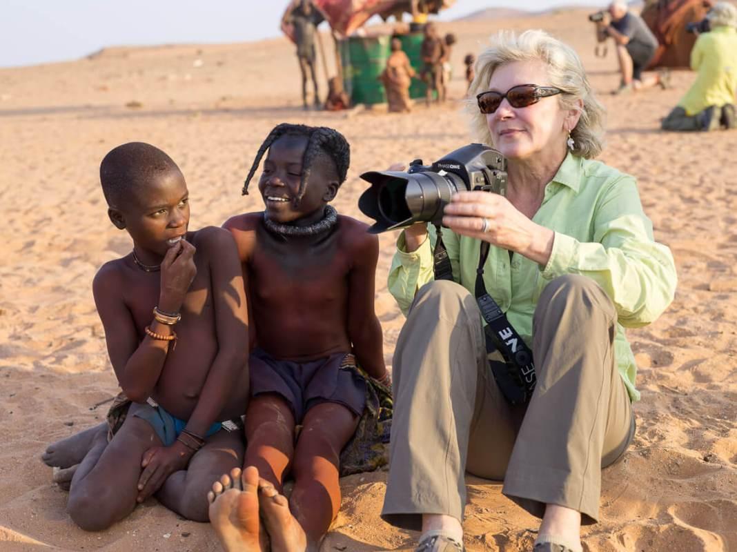Woman photographer sitting next to Himba children