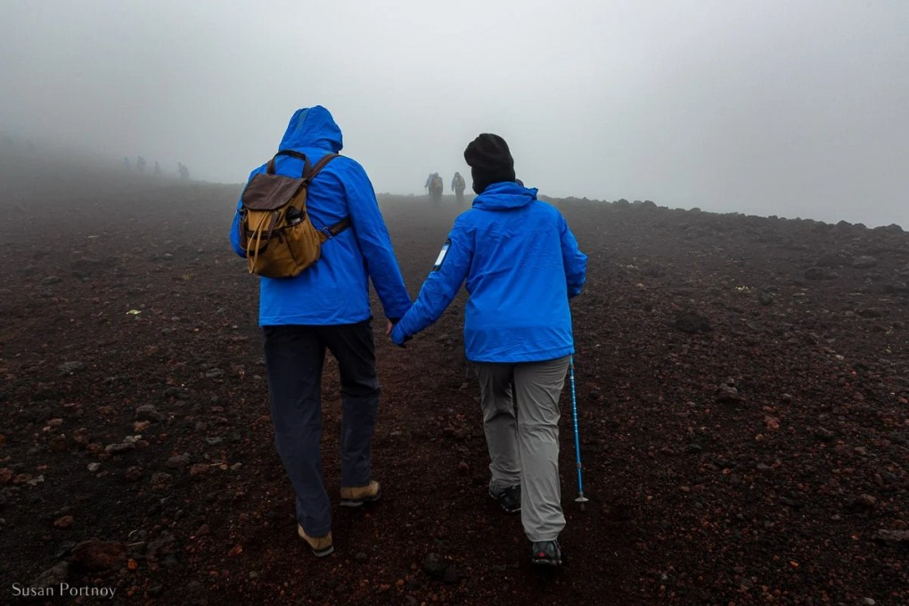 A Couple hold hands while walking on the lava field of Eldfell volcano in the Westman Islands