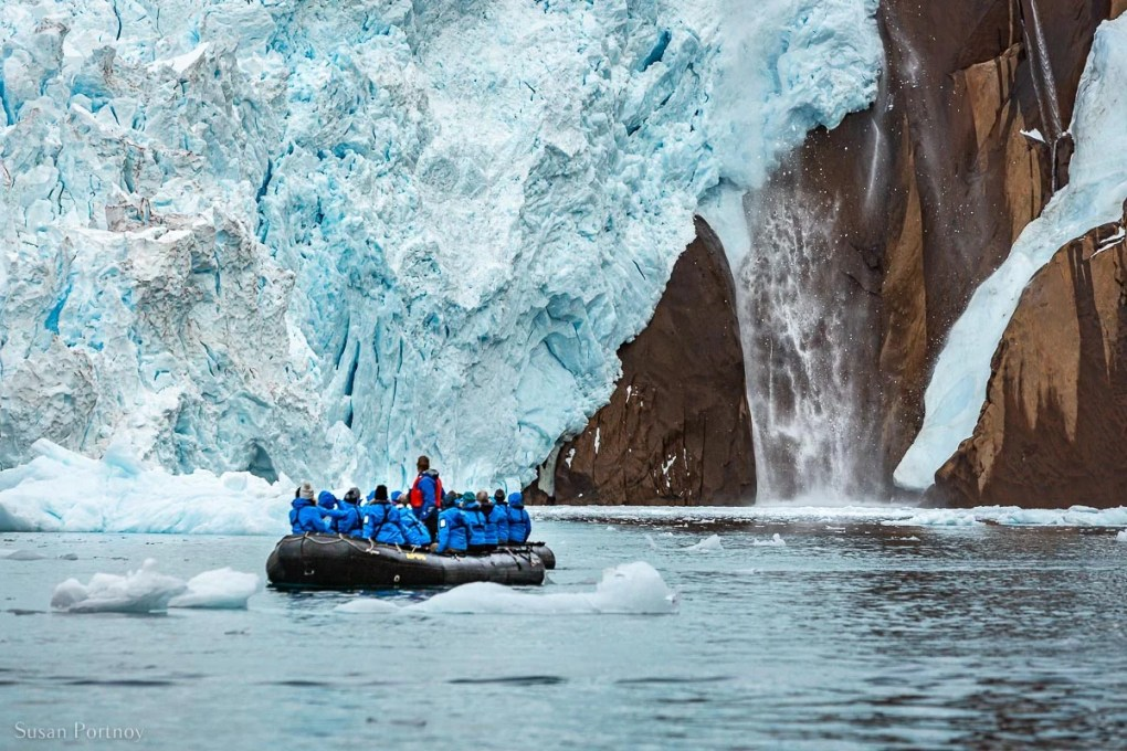 Adventure Canada guests on a zodiac watch ice calve from a tidal glacier