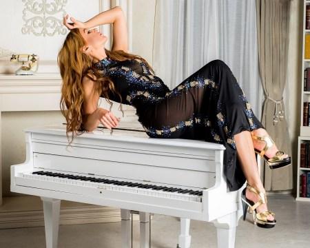 Model on piano. Vikki Lenola wearing Chavez Fashion. London Fashion Week preview.
