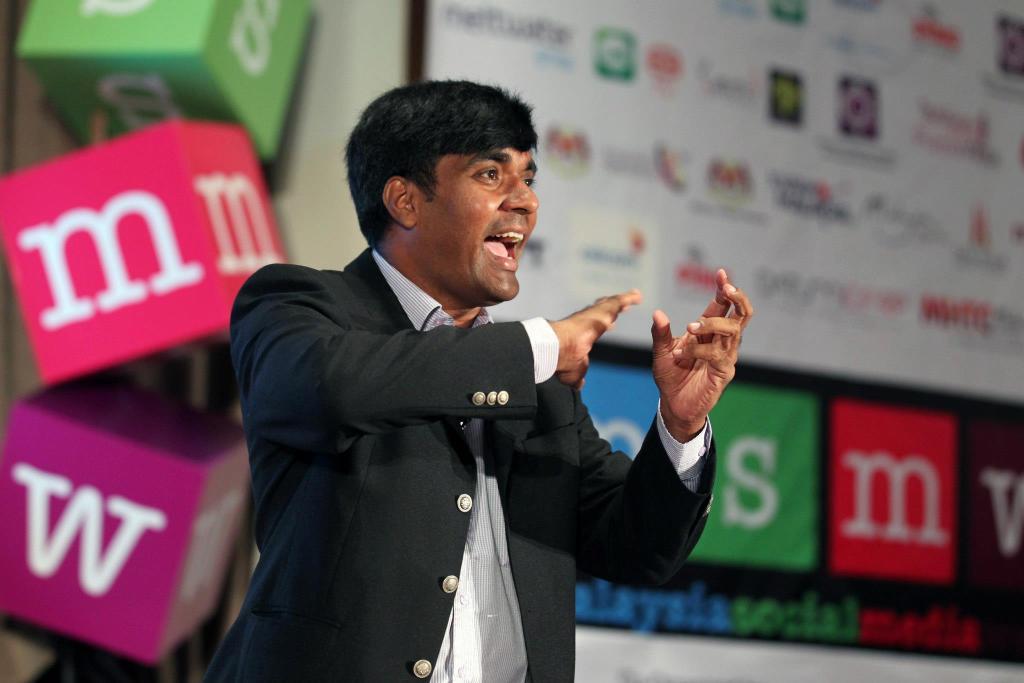 Kiruba Shankar talking on stage wearing black coat