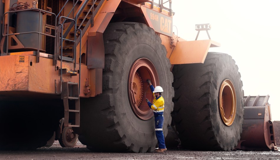 A Kal Tire technician performs a tyre inspection on a CAT 994 wheel loader. Image: Kal Tire