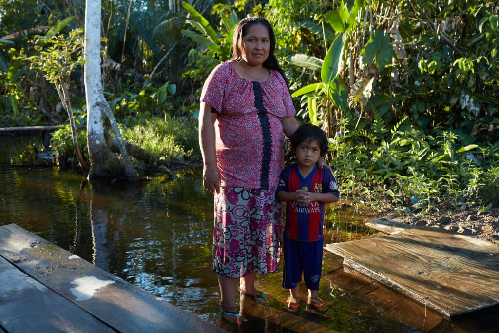 """NUEVO PORVENIR, LORETO, PERU – JULY 9, 2017:<br /><br /><br /><br /><br /> Rosa Nashmate Bapahuiri, age 34, with her son Erudito, age 4: """"When I was a young girl in the 1980s, you could still find good, healthy fish near my village, Lobo Yacu. Now, you have to travel hours in a peke-peke (small motored canoe). Our village is in a floodplain. Every year, when the water rises in the rainy season, the land is contaminated. The soil is not the same. Yucca, plantains, cocona tomatoes — they don't grow well. If you open them, they are dry, dark and boney. They don't develop. Sometimes my parents talk about the abundance they remember, when they would farm so many fruits they would waste them. Now we have a lack of fruits."""" in Nuevo Porvenir, on July 9, 2017. (Photo by Ben Depp)"""
