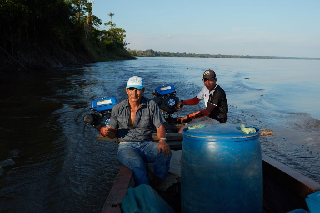 """DOS DE MAYO, PERU – JULY 16, 2017: Apu Alfonso Lopez Tejare, pilots a boat from Naulta to his home village of Dos de Mayo on the MarañónRiver in the State of Loreto, Puru. Alfonso Lopez Tejare is the leader of his community, he say's """"In October 2000, there was a great spill near Saramuro in the Marañón. A black stain covered the river all the way to Nauta, several hours by boat. The company hired us to collect the oil with sticks and mugs and bury it. They gave us no protection. Weeks later, flood season arrived. Our communities and farmlands were flooded with petroleum. The people dug holes and tried to bury it.Even then, we didn't know much about oil. We didn't understand when the media said it would take the heavy metals 30 years to settle in the bottom of the river. But we noticed the fish in the streams were becoming thin and malnourished. Their eggs were small. Before the spill, we would drop a net and catch half-a-ton of fish. After, we caught maybe 30 kilograms of sick fish. People began to be ill. Strange bumps and rashes. Children no longer learned well in school. They had stomachaches and headaches. The traditional medicines did not cure us. We went to the health centers in the cities, but there were no remedies."""" July 16, 2017. (Photo by Ben Depp)"""
