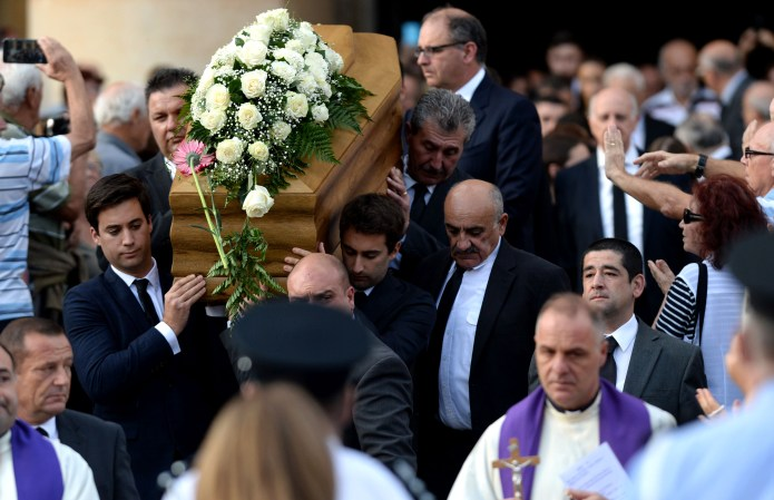 TOPSHOT - The sons of murdered journalist Daphne Caruana Galizia carry the coffin of their mother out of the church in Mosta, on November 3, 2017, after her funeral ceremony. The anti-corruption campaigner will be laid to rest after a service in Mosta, close to the site where the blogger was blown up in a car bombing in an October 16 attack which made headlines around the world. Caruana Galizia, 53, had made repeated and detailed corruption allegations for years against Prime Minister Joseph Muscat's inner circle and had recently turned her investigative scrutiny on the opposition as well. / AFP PHOTO / Matthew Mirabelli / Malta OUT (Photo credit should read MATTHEW MIRABELLI/AFP/Getty Images)