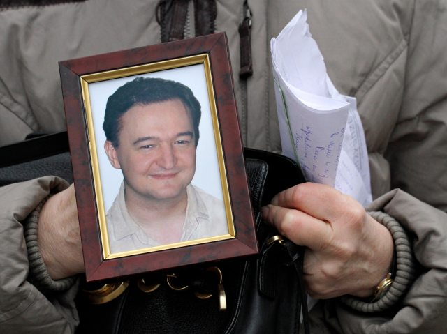 FILE - In this Nov. 30, 2009 file photo, Nataliya Magnitskaya holds a portrait of her son Sergei Magnitsky, a lawyer who died in jail, as she speaks with The Associated Press in Moscow, Russia. British officials are investigating the unexplained death of a Russian businessman, a key witness against Russian officials who allegedly stole $230 in a money laundering scheme. Alexander Perepilichny's body was discovered in the grounds of his rented house south of London. Police said a post-mortem on the 44-year-old former milk factory owner would begin Friday Nov. 30, 2012, but it was unclear when results would be released. Toxicology results could take months, according to Surrey Police spokeswoman Nicola Burress. At the center of the latest Russian death is Sergei Magnitsky, a lawyer who was hired by the London-based Hedge Fund Hermitage Capital to investigate the alleged money laundering scheme and died in a Moscow jail in 2009 amid torture claims. His death has since spurred efforts in Europe and the U.S. to punish Russian officials who may have been complicit in human rights abuses. (AP Photo / Alexander Zemlianichenko, File)