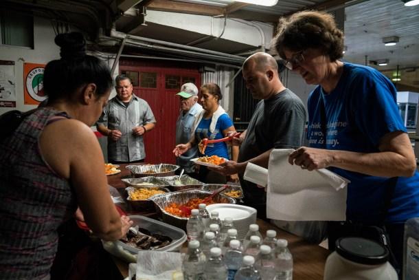Volunteers Michael Benavides, center left, Rolando Covar, wearing a cap, and Andrea Rudnik, far right, deliver food to people waiting to seek asylum in the U.S. near the Gateway International Bridge in Matamoros, Tamaulipas on Nov. 5, 2018. Photo: Verónica G. Cárdenas for The Intercept