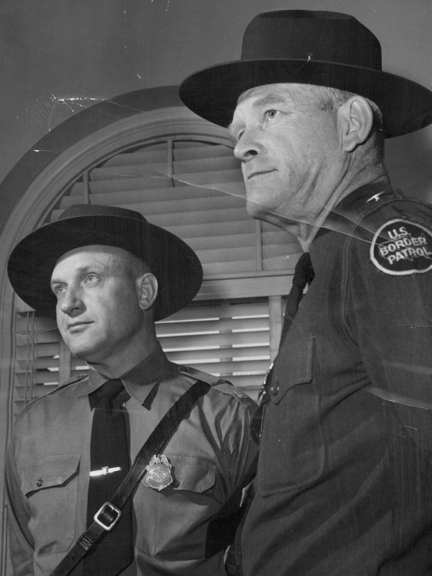 MAY 11 1955; In Denver to recruit men for 'hazardous' jobs with the U. S. border patrol are John P. Longan (left), 40, and Owen S. Juvrud, 47, both senior patrol inspectors stationed at El Paso, Tex. Written examinations for border patrol jobs, paying from $3,795 up to $12,000 annually for career employes, are given at 6 p. m. every Wednesday through June 29 in room 417 of the postoffice.;  (Photo By Dean Conger/The Denver Post via Getty Images)