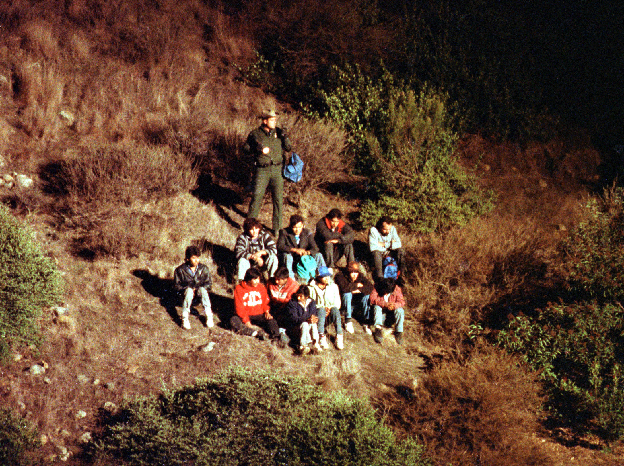 Illegal Mexican immigrants being searched by US Border Patrol agent (back). They're being illuminated on a steep canyon hillside by a border patrol helicopter orbiting overhead.  (Photo by Dave Gatley/Mai/Mai/The LIFE Images Collection/Getty Images)