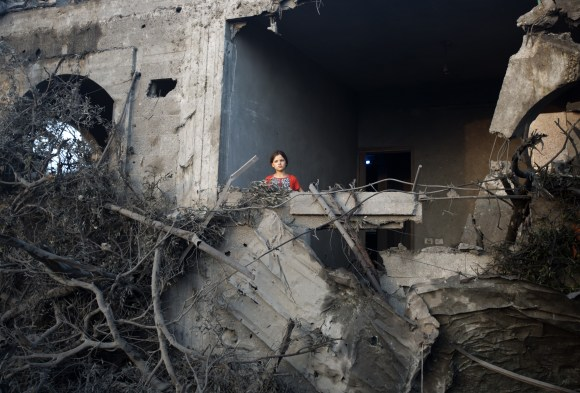 A Palestinian girl stands in a destroyed building following an Israeli military strike in  Gaza City on July 08, 2014 . The Israeli air force launched dozens of raids on the Gaza Strip overnight after massive rocket fire from the enclave pounded southern Israel, leaving 17 people injured, sources said. AFP PHOTO / MAHMUD HAMS        (Photo credit should read MAHMUD HAMS/AFP via Getty Images)