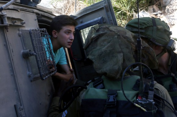 TOPSHOT - Israeli soldiers free a Palestinian youth, after temporarily detaining two youth, in the West Bank village of Burin on September 15, 2016, following scuffles with Israeli settlers. / AFP / JAAFAR ASHTIYEH