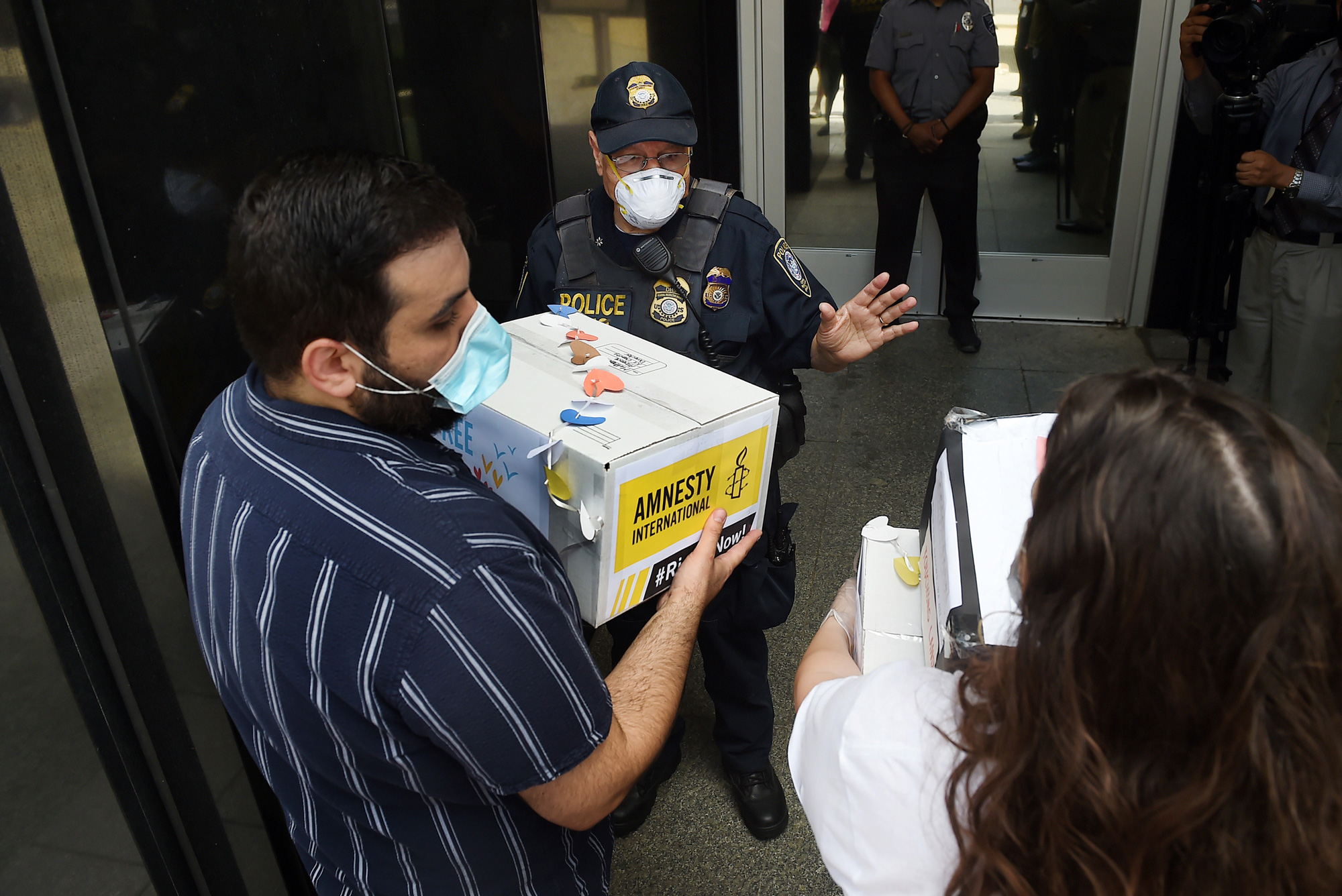 Activists try to deliver a petition to demand the release of immigrants families in detention centers at risk during the coronavirus pandemic, outside the Immigration and Customs Enforcement (ICE) headquarters in Washington, DC, on July 17, 2020. - Lawmakers have raised concerns about the spread of the virus inside detention centers across the country as more than 3,000 immigrants in ICE custody have tested positive for COVID-19. (Photo by Olivier DOULIERY / AFP) (Photo by OLIVIER DOULIERY/AFP via Getty Images)