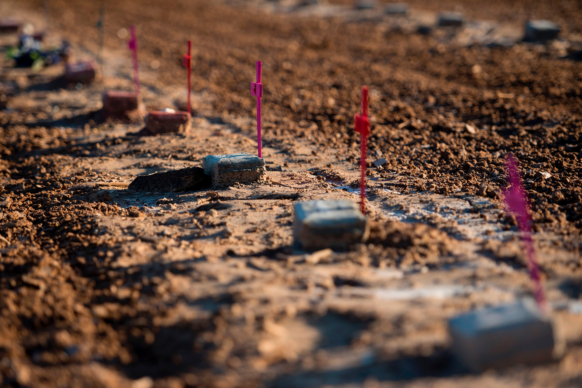 """TOPSHOT - Bricks inscribed with the words """"John Doe"""" lie in an unmarked dirt lot at the end of Terrace Park Cemetery in Holtville, California on February 14, 2017, where the remains of hundreds of unidentified migrants are buried.  Attention Editors, this image is part of an ongoing AFP photo project documenting the life on the two sides of the US/Mexico border simultaneously by two photographers traveling for ten days from California to Texas on the US side and from Baja California to Tamaulipas on the Mexican side between February 13 and 22, 2017. You can find all the images with the keyword : BORDERPROJECT2017 on our wire and on www.afpforum.com / AFP PHOTO / JIM WATSON        (Photo credit should read JIM WATSON/AFP via Getty Images)"""
