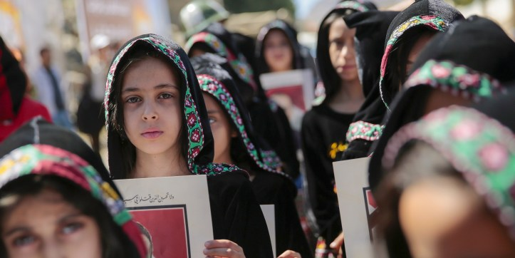 Yemeni girls hold pictures of civilian victims during a demonstration to commemorate the first anniversary of the Saudi-led airstrike in which 140 civilians were killed and more than 500 were injured, in Sanaa, Yemen, on Oct. 8, 2017.