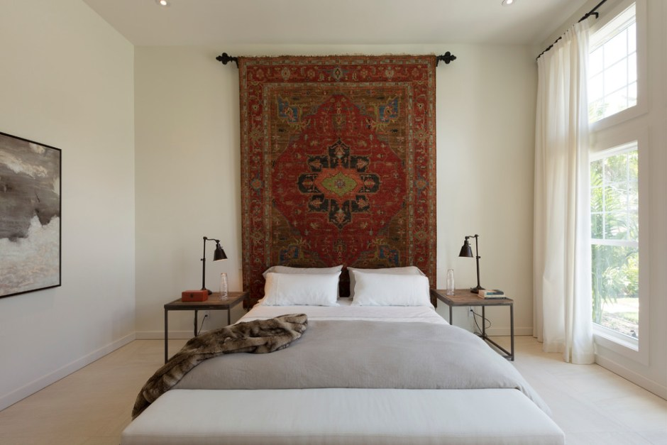 ADD TEXTURE TO YOUR WALLS WITH DECORATIVE WALL HANGINGS | This vintage find rug, has been used as an alternative to a headboard and adds warmth and depth to this minimalist bedroom space.