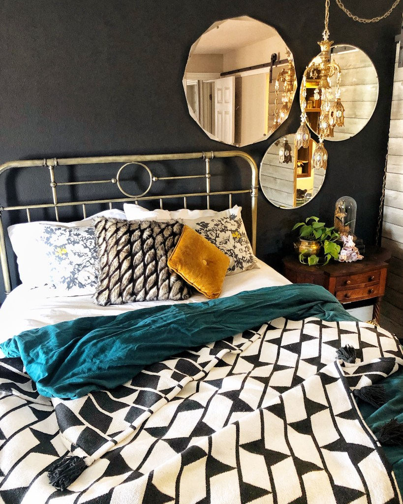An Eclectic '70s Home Filled With Vintage Finds - Jenasie Earl | Bedroom with dark walls are lifted by adding pops of pattern and colour as well as texture. Vintage mirrors and lighting add light reflective decorative elements.